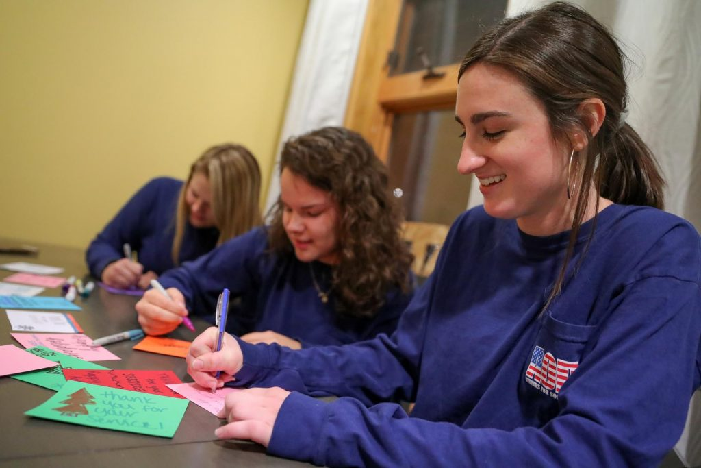 Cassie Kenedy of Omaha, right, Lindsay Bover of Grand Island, center, and Lauren Rezac of Brainard write Christmas cards to service men and women as part of Alpha Omicron Pi's Sisters for Soldiers event. (Photo by Corbey R. Dorsey, UNK Communications)