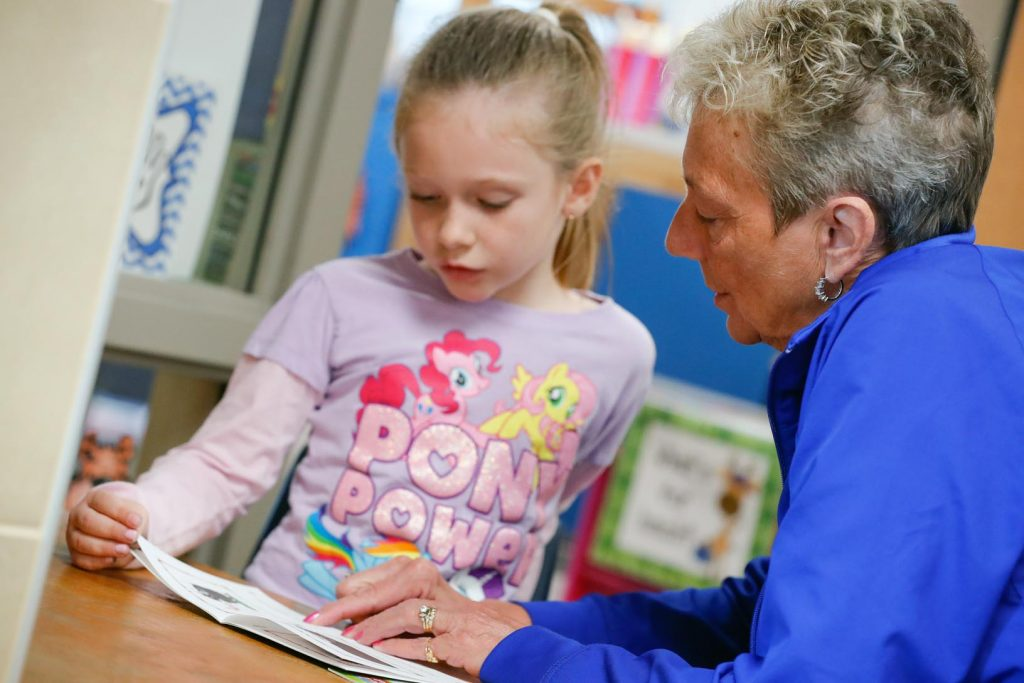 Members of the UNK swimming and diving team work with students at Kenwood Elementary School in Kearney through the new Loper AthLEADS program. Head coach Becky O'Connell is pictured reading to a kindergartner during a recent visit. (Photo by Corbey R. Dorsey, UNK Communications)