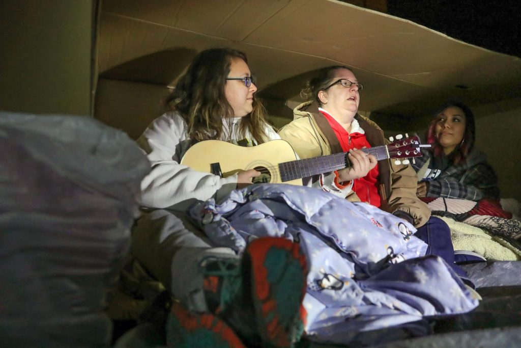 "UNK students, from left to right, Sadie Brandt, Carrie Hardage and Jayme Gomez, all of Kearney, slept outside in cardboard boxes Friday as part of Chi Sigma Iota's ""A Night Without a Home,"" which raises awareness about homelessness. (Photo by Corbey R. Dorsey, UNK Communications)"