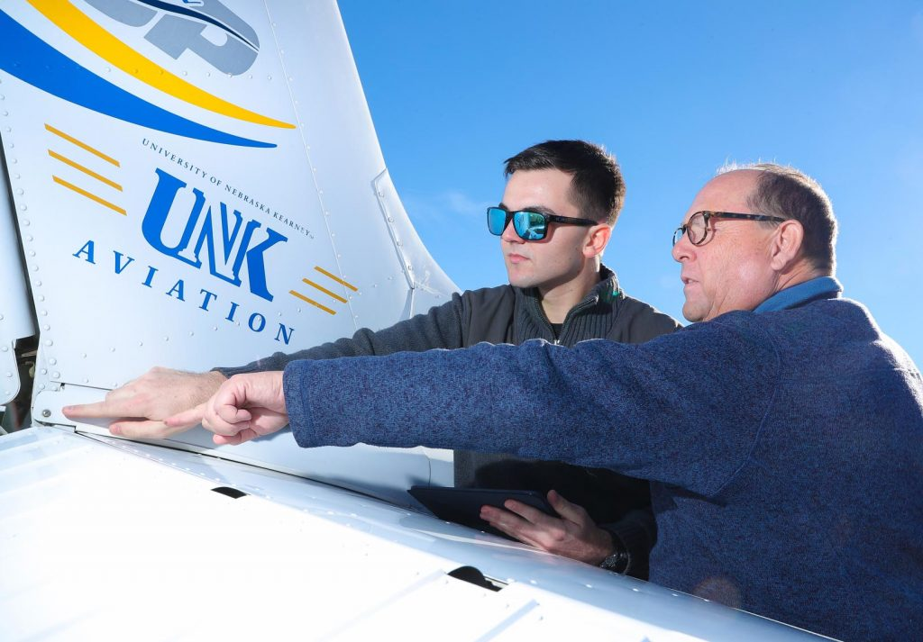 "Colton Rolls, left, a senior from Alliance, says the strength of UNK's aviation program comes from Terry Gibbs, right, and the other instructors. ""He does a great job of explaining everything we need to know both inside and outside the cockpit,"" Rolls said of Gibbs, who's been the program's director since 2001. (Photo by Corbey R. Dorsey, UNK Communications)"