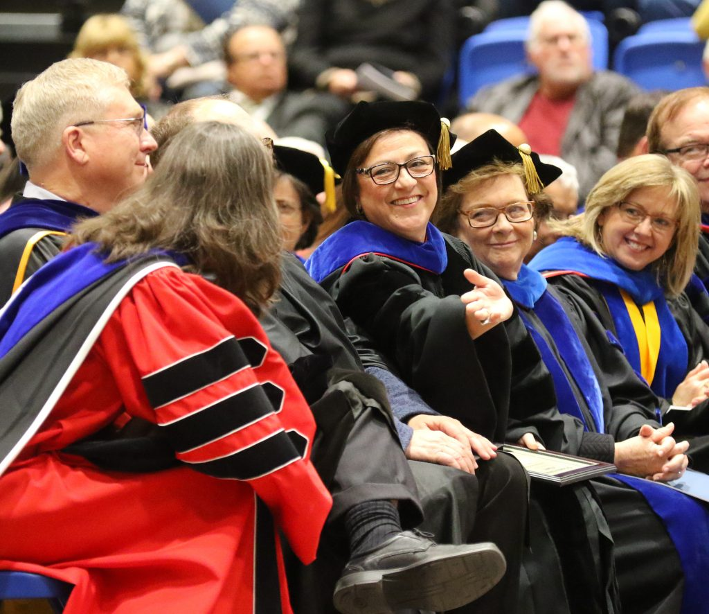 Maha Younes, center, a professor in UNK's Department of Social Work, participates in Friday's winter commencement, where she received the Leland Holdt/Security Mutual Life Insurance Company Distinguished Faculty Award. (Photo by Todd Gottula, UNK Communications)